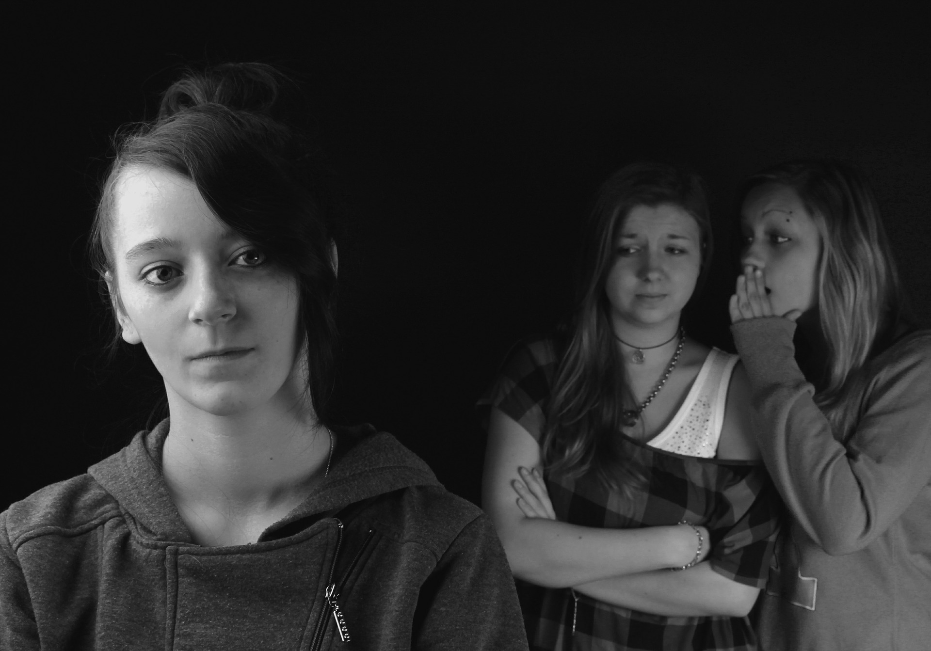 A teenager alone with two other teenagers gossping about her in the background