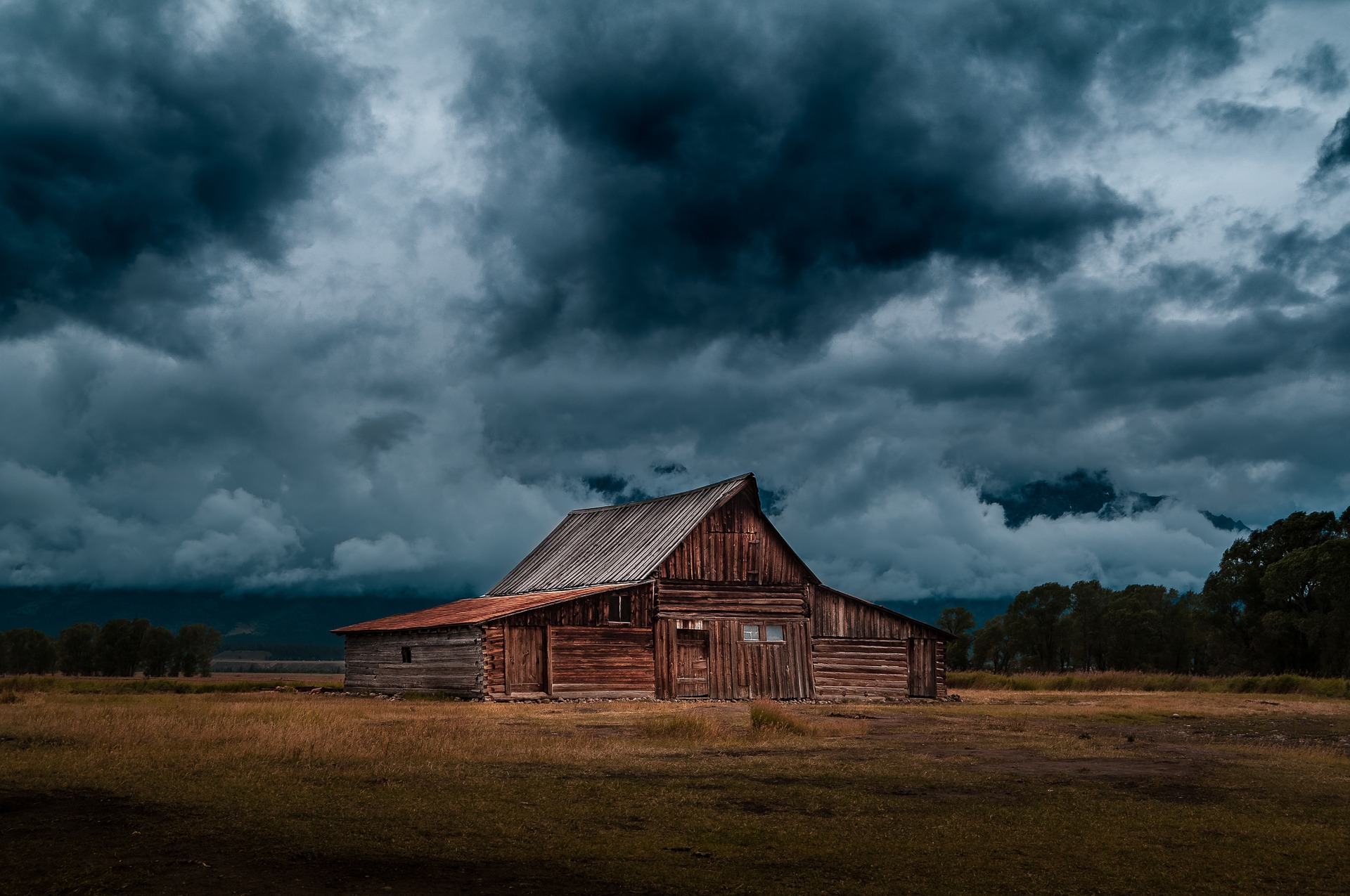 A cabin on a plain under clouds on a very dark day