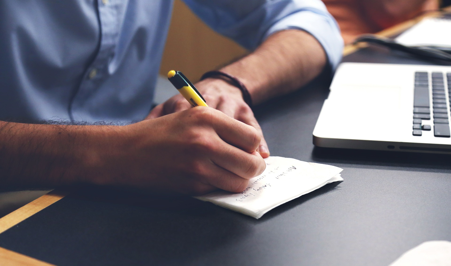 A man taking notes on paper on a desk.
