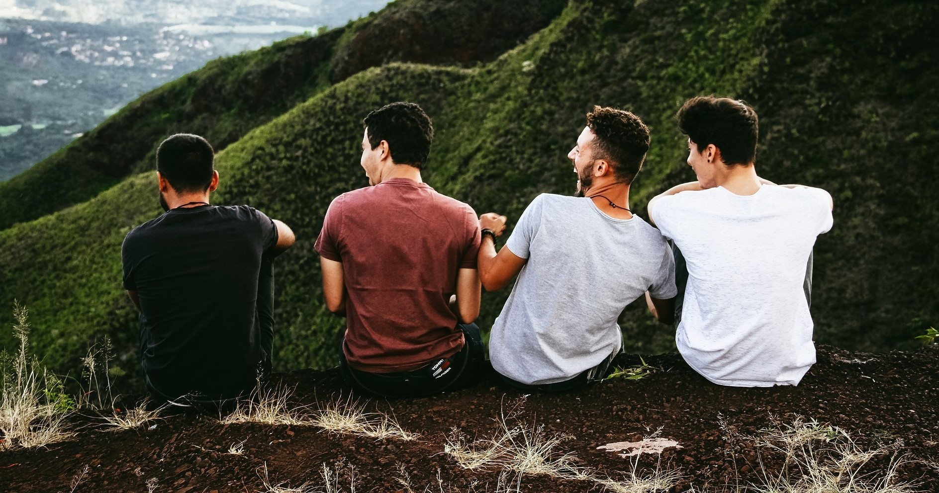 Four friends laughing and hanging out outside