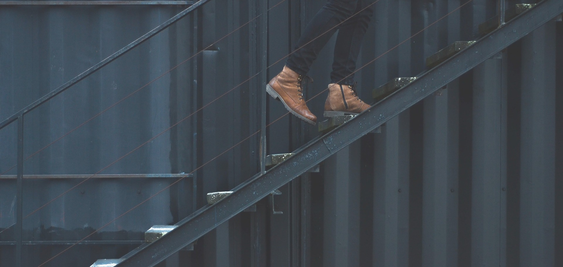 A staircase seen from the side, showing the boots of someone walking up.