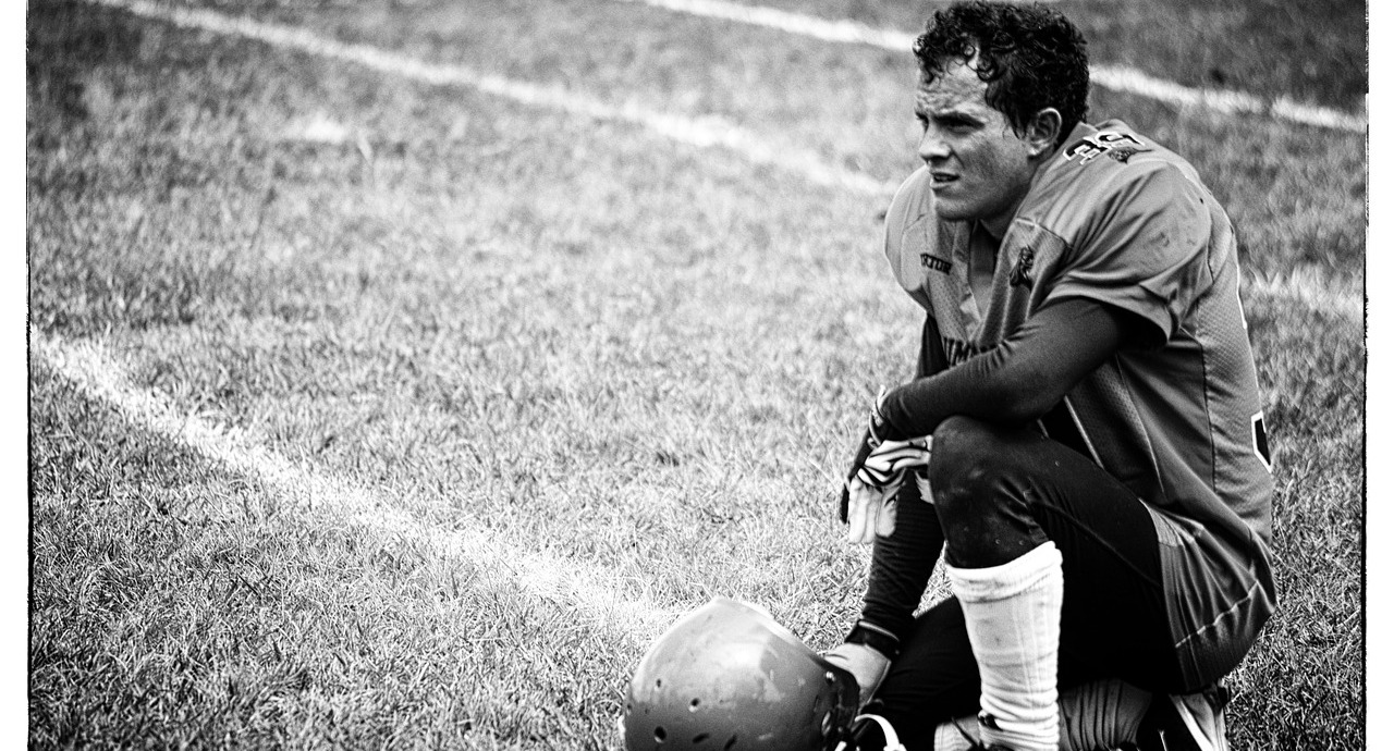 An Athlete kneeling on a field next to his helmet
