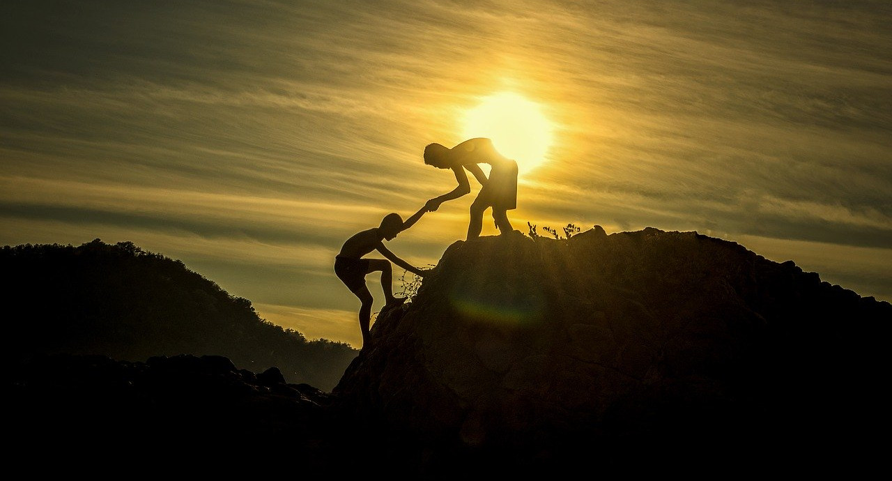 a silhouette of one person helping another person climb a hill