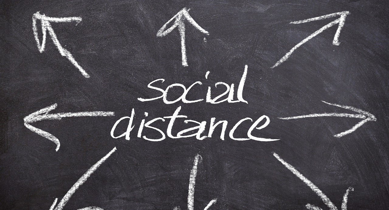 """""""social distance"""" written on a chalkboard with arrows pointing outward in all directions"""